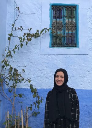 Yasmeen Ragab pictured outside, next to a tree and blue wall